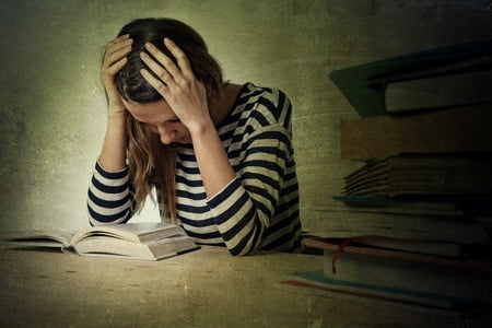 41754592 - young stressed student girl studying pile of books on library desk preparing mba test or exam in stress feeling tired and overwhelmed in youth education concept grunge messy background style