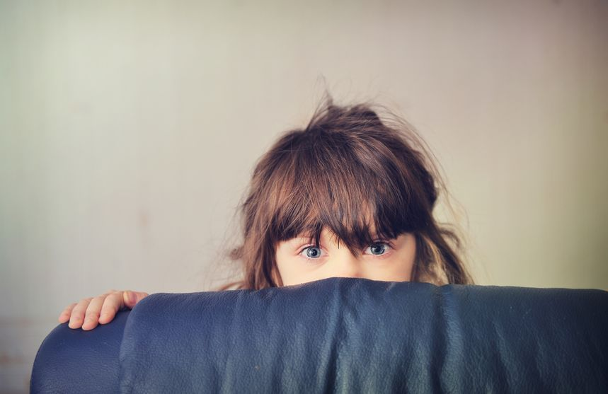 11488605 - little girl playing hide and seek behind the sofa bed