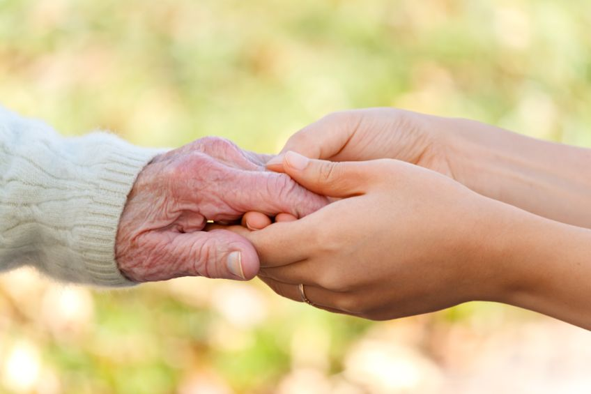 11324542 - senior and young holding hands outside