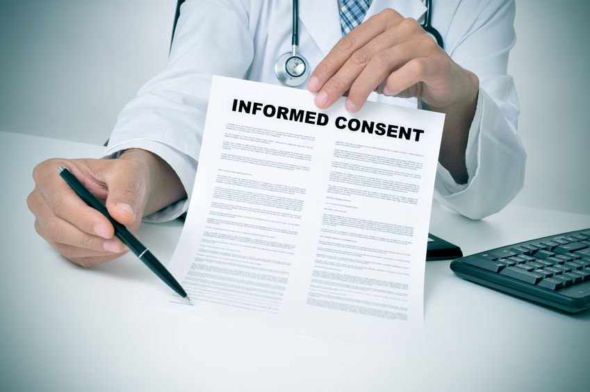 27915570 - a doctor in his office showing an informed consent document and pointing with a pen where the patient must to sign